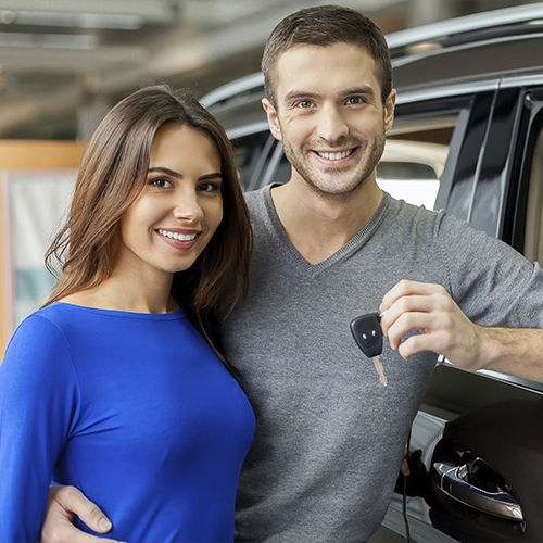 Couple in front of their car holding the key